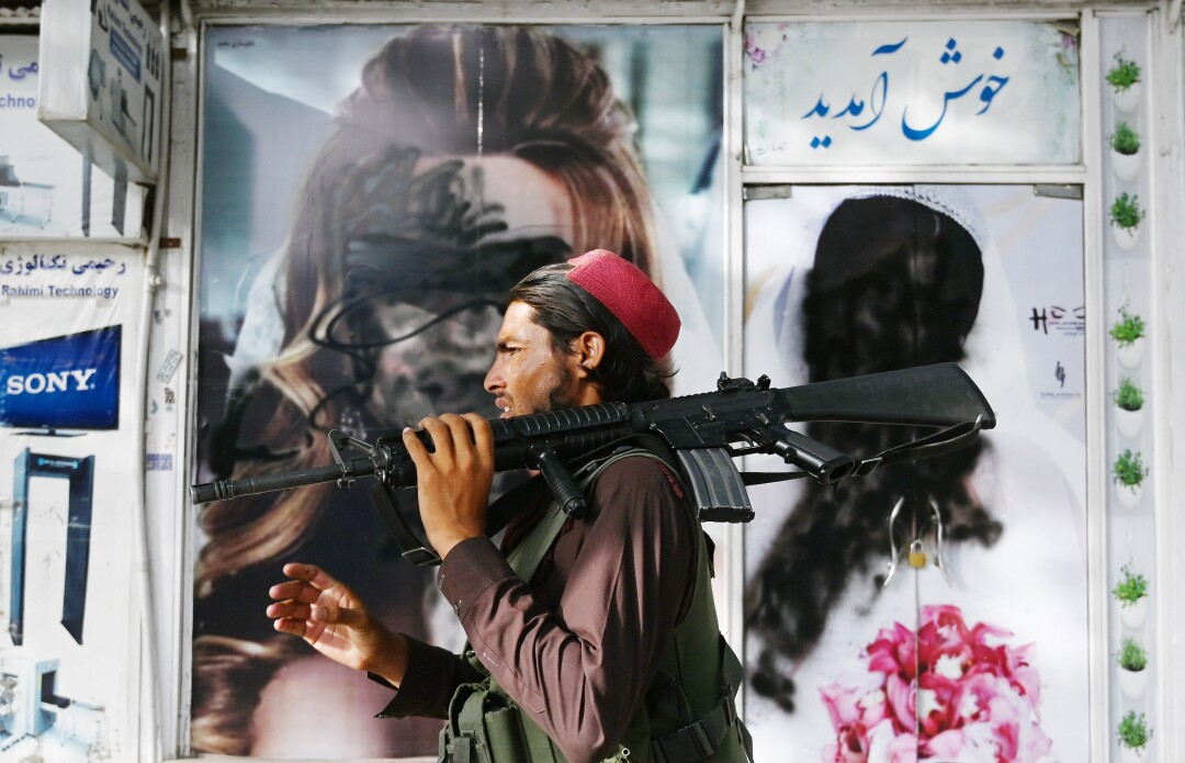 A Taliban fighter holding a gun on his shoulder walks past images of women that have been obscured by paint.