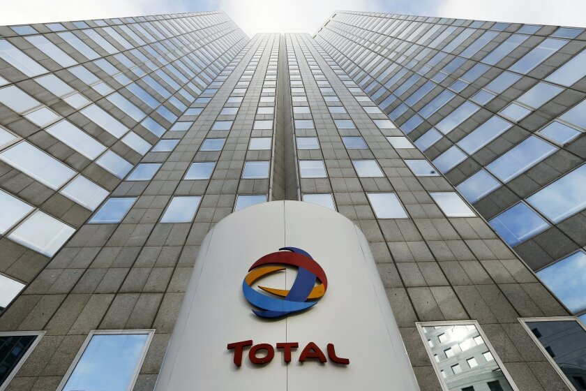FILE - In tjhis Feb.5, 2013 file photo, the logo of the French oil giant Total SA is seen at the entrance of the company headquarters in the La Defense business district, west of Paris. The French company said Thursday Feb.11, 2016 that profit adjusted for changes in the value of inventories and on