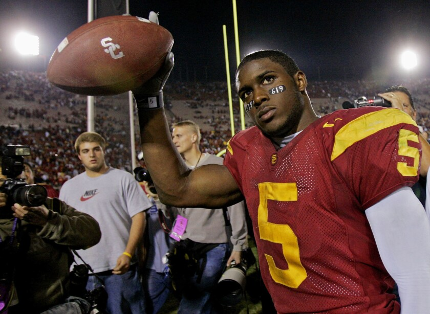 """FILE - In this Nov. 19, 2005, file photo, Southern California tail back Reggie Bush walks off the field holding the game ball after the Trojans defeated Fresno State, 50-42, at the Los Angeles Coliseum. The former star running back had been prohibited from interacting in an official capacity with the school he played for from 2003-05 since NCAA sanctions handed down in 2010. Bush and USC were penalized for him and his family receiving impermissible benefits while he was still in school. USC President Carol Folt wrote in a letter to Bush on Wednesday, June 10, 2020, that he could now """"be afforded the privileges and courtesies extended to all Trojan football alums.""""(AP Photo/Kevork Djansezian, File)"""