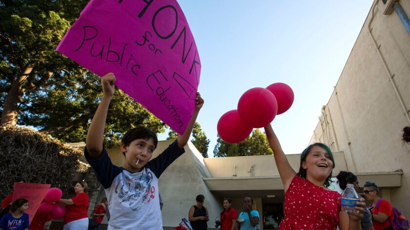 Students drum up support for Prop. 51, a school-construction bond measure, and Prop. 55, an extension of higher taxes on the wealthy, outside of their elementary school in October of 2016.