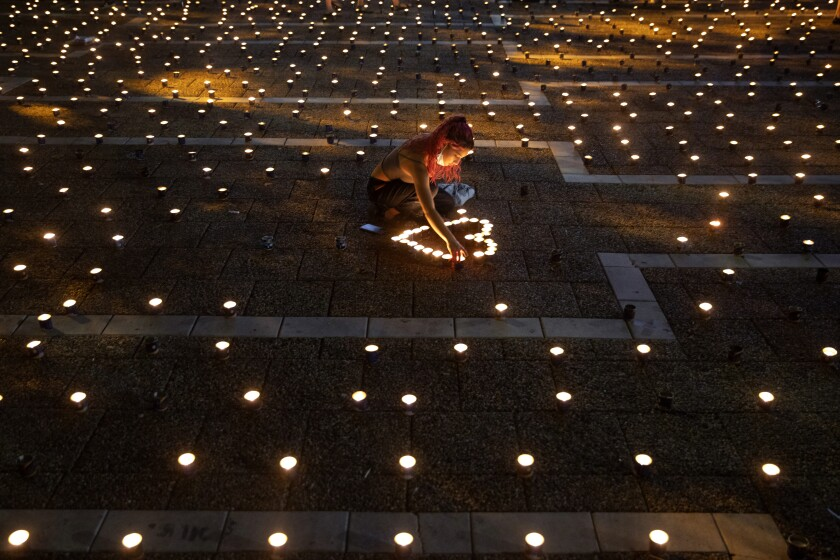 A woman lights memorial candles on the 25th anniversary of the assassination of Israeli Prime Minister Yitzhak Rabin, at Rabin Square, Tel Aviv, Israel, Thursday, Oct. 29, 2020. (AP Photo/Oded Balilty)