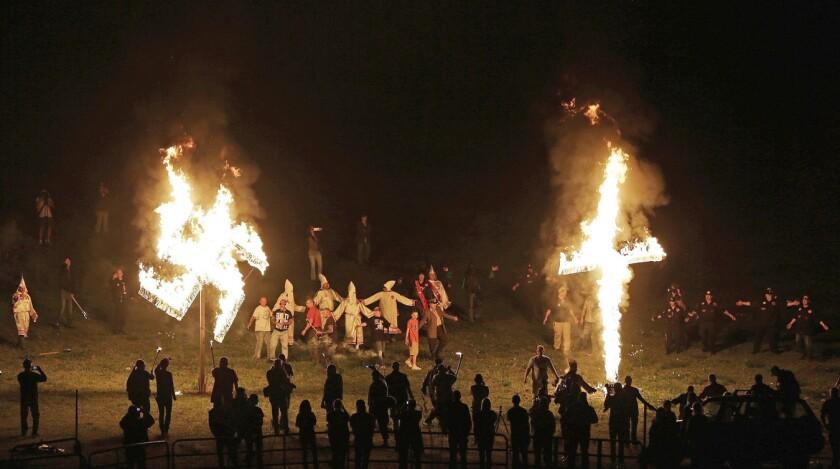 """Miembros del Ku Klux Klan queman una cruz y una esv·stica durante un acto para exaltar el """"orgullo blanco"""" cerca de Cedar Town, Georgia, el 23 de abril del 2016. 150 aÒos despuÈs de su nacimiento, el KKK sigue vigente, aunque con muchos menos afiliados que en sus mejores momentos, y se enfoca en su oposiciÛn a la inmigraciÛn, no en los derechos civiles de los negros. (AP Photo/Mike Stewart)"""
