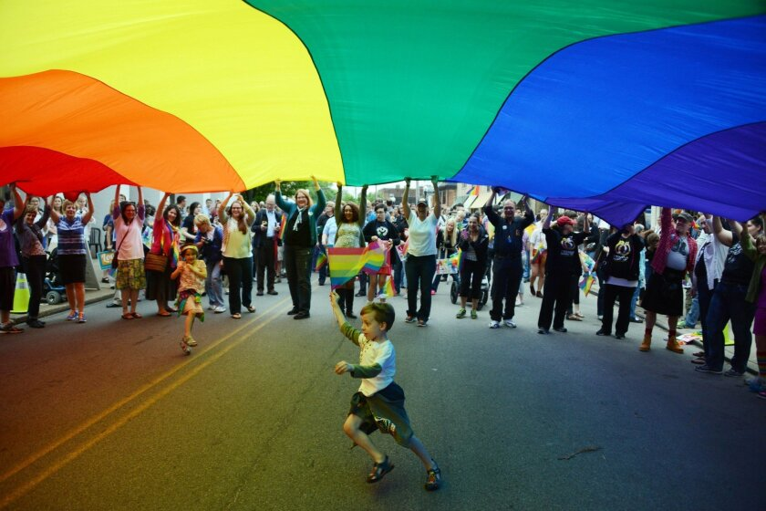 Elijah Socie, 6, of Pittsburgh runs under a pride banner while carrying a pride flag to celebrate a ruling overturning Pennsylvania's gay marriage ban.