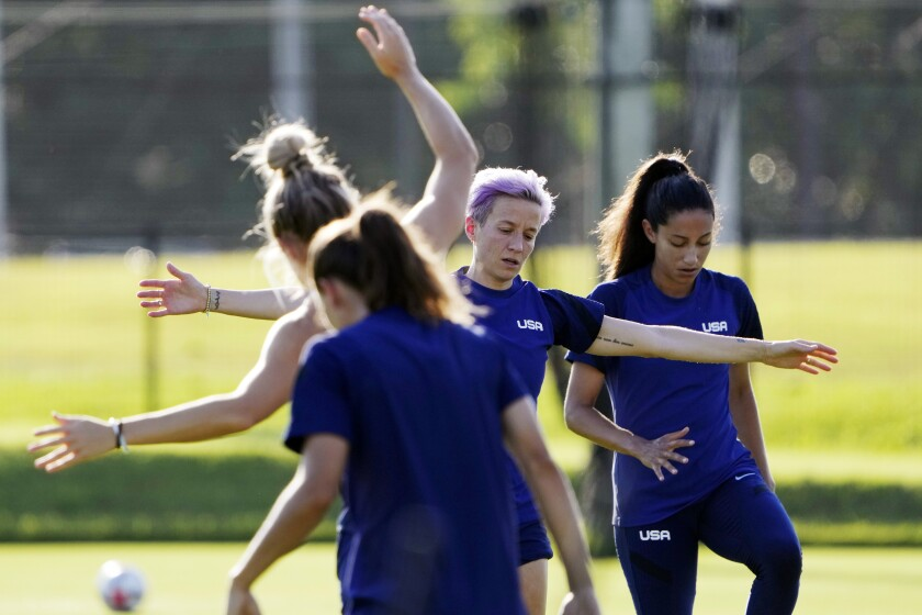 Megan Rapinoe, second right, and her teammates warm up in Tokyo