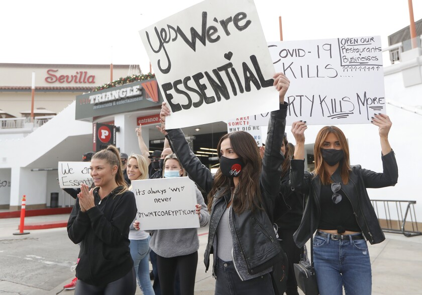 Demonstrators protest the stay-at-home order at Triangle Square in Costa Mesa.