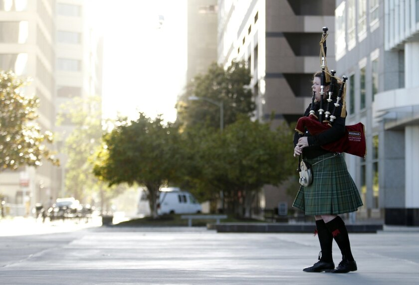 Claire Raftery, of the Irish Pipes of San Francisco, plays the bagpipes before a memorial service for six Irish students at the Cathedral of Christ the Light Wednesday, June 17, 2015, in Oakland, Calif. The six Irish students died when a balcony collapsed during a party in Berkeley. (AP Photo/Beck Diefenbach)