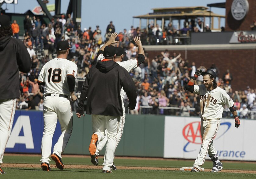 San Francisco Giants' Brandon Crawford, right, is greeted by teammates after hitting the game-winning single off San Diego Padres relief pitcher Brad Hand during the 10th inning of a baseball game Wednesday, May 25, 2016, in San Francisco. San Francisco won 4-3. (AP Photo/Eric Risberg)