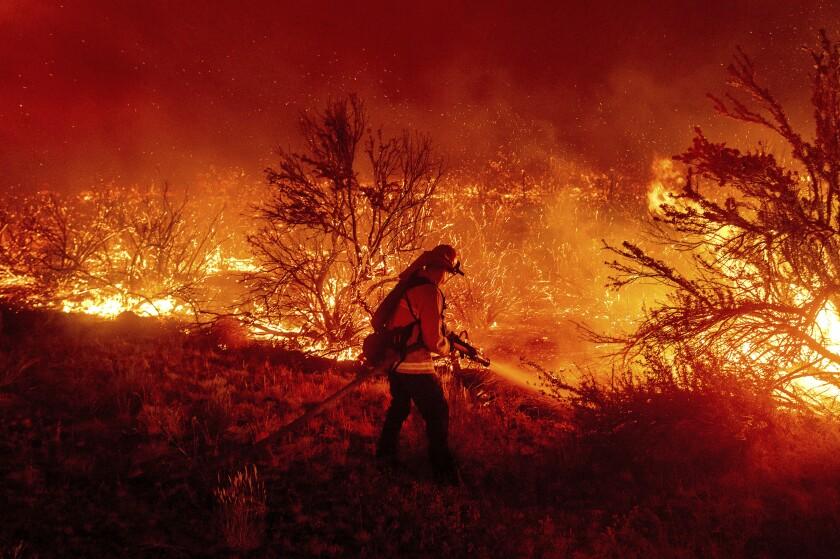 A firefighter battles the Dixie fire