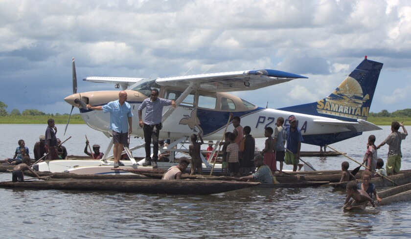 Mark Palm and his float plane are greeted by Papua New Guinea natives to whom he delivers emergency aid.