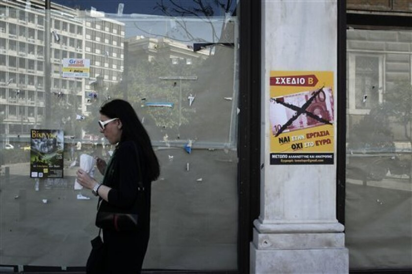 A woman passes outside a closed shop as a poster reads in Greek '' yes to work, no to the euro''  in Athens, Wednesday, April 10, 2013.  The European Union's statistics agency, Eurostat, on Wednesday said that labor costs had sunk 11.2 percent in recession-hit Greece between 2008 and 2012, compared