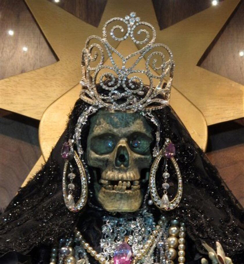 In this Feb. 12, 2013 photo, a statue of La Sante Muerte from an altar run by Arely Vazquez Gonzalez, a Mexican immigrant and transgender woman, is shown at inside a Queens, NY apartment.  La Santa Muerte, an underworld saint most recently associated with the violent drug trade in Mexico, now is sp
