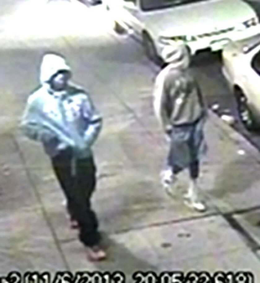 Police are searching for two men who were caught on surveillance video walking along a sidewalk in Pico-Union near where Atilio Benavides-Amaya was killed Nov. 6, 2013.