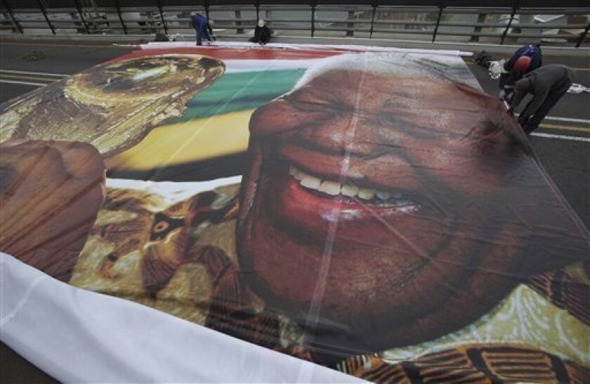 In this photo taken Sunday May 30, 2010 workers prepare to hang an image of former President Nelson Mandela with the World Cup trophy on the Mandela bridge leading to downtown Johannesburg. A spokesman for South Africa's ruling party aid Thyrsday, May 3 2010, that Mandela will attend the opening and clsoing matches of the World Cup. (AP Photo/Denis Farrell)