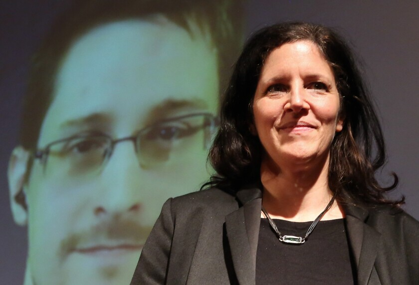 BERLIN, GERMANY - DECEMBER 14: Filmmaker Laura Poitras speaks as former National Security Agency (NSA) contractor turned whistleblower Edward Snowden is seen on a video conference screen during an award ceremony for the Carl von Ossietzky journalism prize on December 14, 2014 in Berlin, Germany.