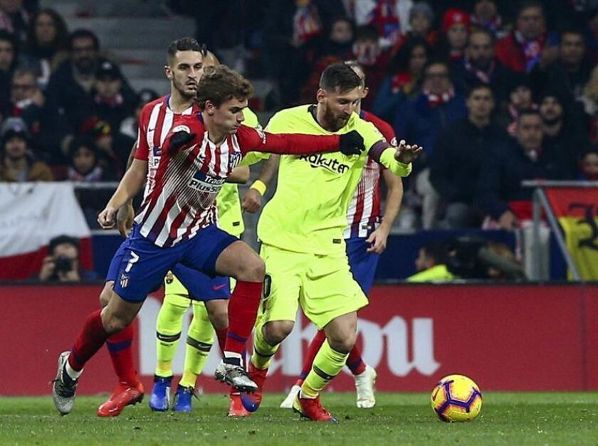 El delantero francés del Atlético de Madrid Griezmann (i) pelea un balón con Leo Messi, del FC Barcelona, durante el partido de Liga en Primera División que disputaron en el estadio Metropolitano, en Madrid. EFE