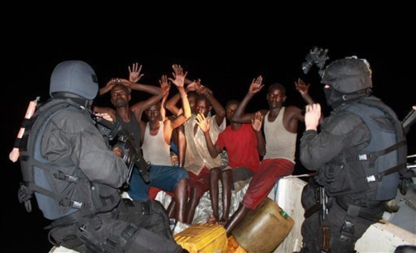 In this image made available by NATO in London, Monday Nov. 30, 2009, Portuguese Naval Marines from the frigate 'Alvares Cabral', guard a group of Somali pirates, during a joint operation with Seychelles and EU forces in the Somali Basin, off the Seychelles, Sunday Nov. 29, 2009, against a pirate group that had attacked the-Spanish flagged fishing vessel 'Ortube Berria'. Involved on the operation, besides the NATO flagship, were the Seychelles Patrol Boat 'Andromache' and two Maritime Patrol Aircraft's from the EU Task-Force also operating in the area on counter-piracy mission. The aircrafts detected and tracked the pirate attacking group composed by a mother-ship and two smaller attack skiffs.(AP Photo/Carlos Dias, NATO, ho)