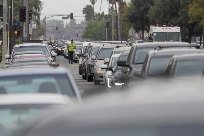 Cars line up on Sepulveda Boulevard to get meal packages provided by LAUSD at a grab-and-go food center at Francisco Sepulveda Middle School in North Hills.