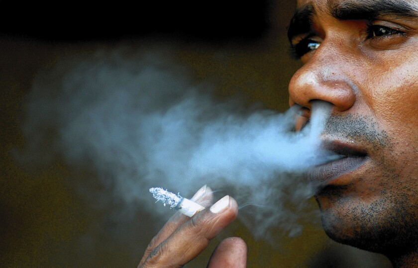 """An Indian man smokes a cigarette on """"World No Tobacco Day"""" in Mumbai."""