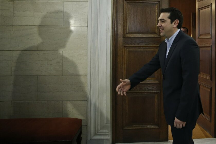 The shadow of Eurogroup chairman Jeroen Dijsselbloem is cast on a wall as Greek Prime Minister Alexis Tsipras waits to greets him during their meeting in Athens, Friday, Jan. 30, 2015. Dijsselbloem is in Athens for talks with Greece's new left wing government after it promised to renege on key bail