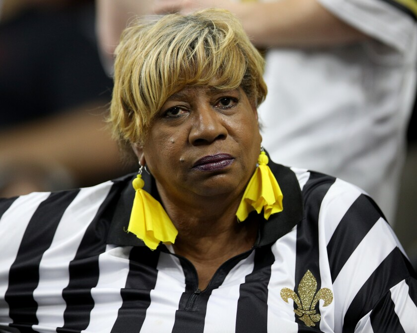 A New Orleans Saints fan in referee attire looks on before a game in 2018.