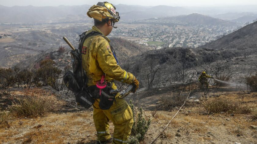 Firefighters take care of hot spots from the Holy Fire near Lake Elsinore.