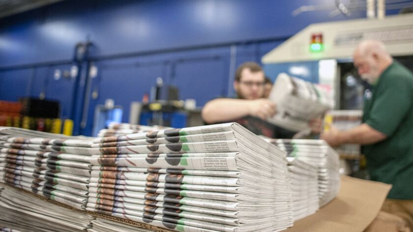 FILE - In this April 11, 2018, file photo, production workers stack newspapers onto a cart at the Ja
