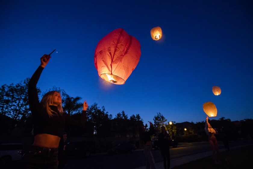 Madison Moore launches a paper lantern into the night during a surprise 16th-birthday celebration for her Tuesday in Huntington Beach.