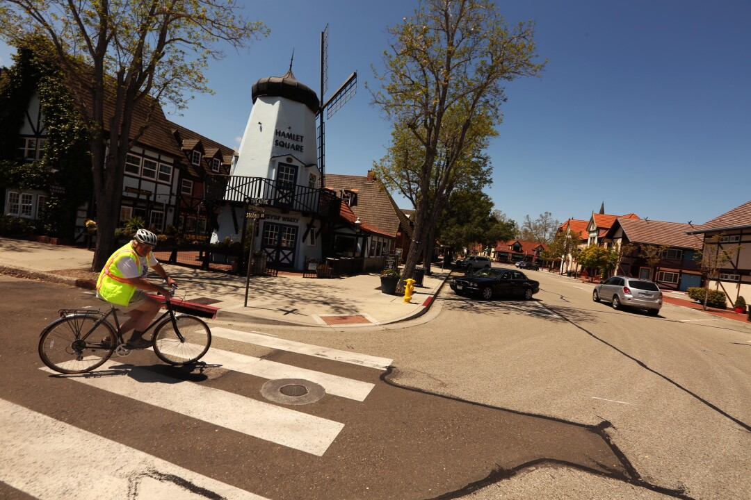 Chuck Stacy, 72, bikes down a street that is usually filled with cars and tourists in downtown Solvang last week.