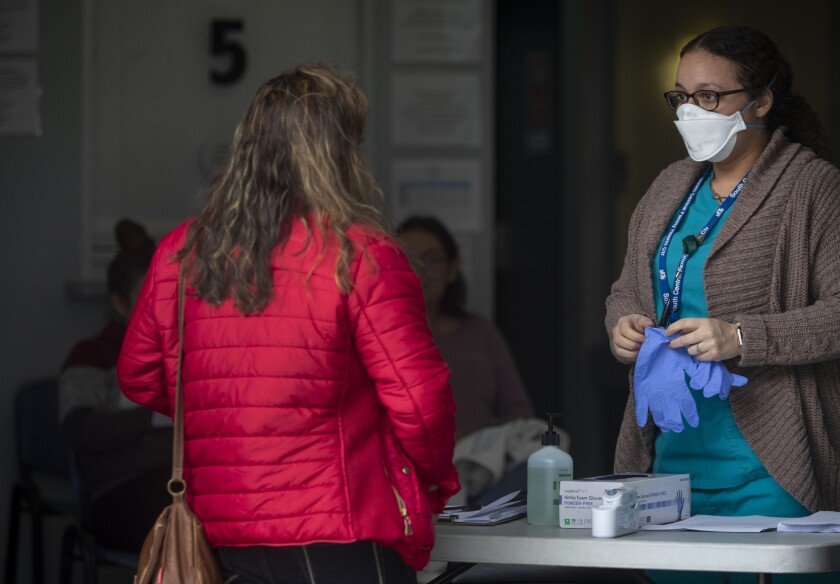 A medical assistant checks people's temperatures outside a clinic that supports victims of domestic violence.