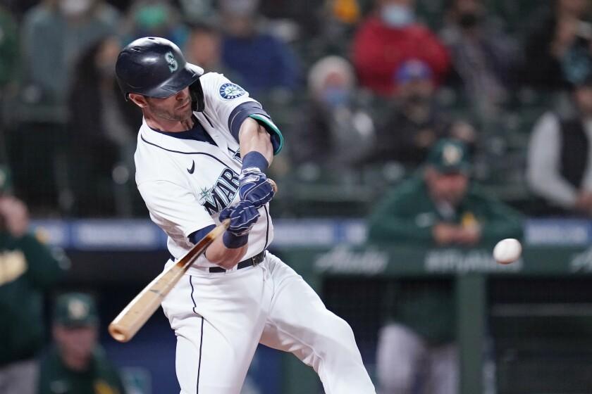 El jugador de los Marineros de Seattle Mitch Haniger pega un jonrón de tres carreras contra los Atléticos de Oakland en el cuarto inning de su juego de béisbol el lunes 27 de septiembre de 2021, en Seattle. (AP Foto/Elaine Thompson)
