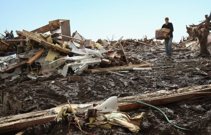 Matt Johnson salvages items from his grandparent's Moore, Okla., home after a powerful tornado ripped through the neighborhood.