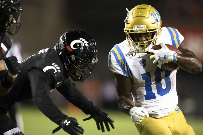 Cincinnati safety Darrick Forrest, left, forces UCLA running back Demetric Felton out of bounds during the second half of the Bruins' loss on Thursday.
