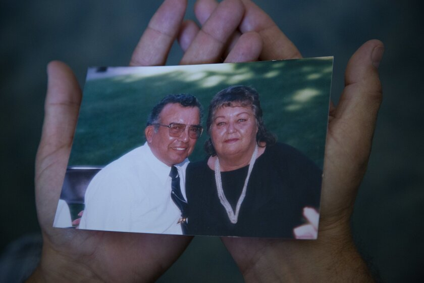 Tony Martinez holds a photo of his parents, Larry and Valorie Martinez, who he cared for before they died.