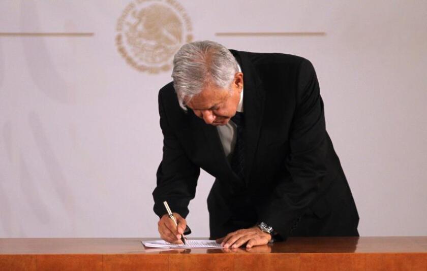 El presidente de México, Andrés Manuel López Obrador, firma una carta en la que se compromete a someterse a una consulta sobre la revocación de mandato. EFE/Archivo