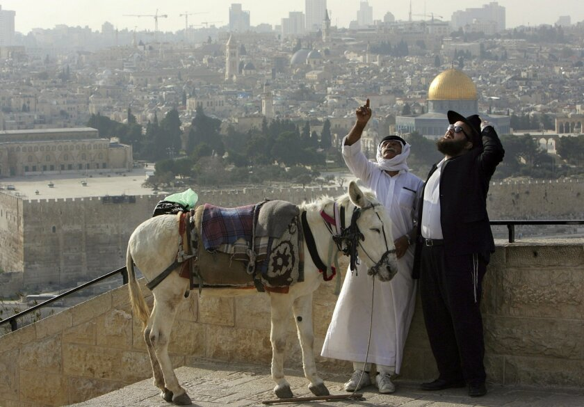 FILE - In this Feb. 22, 2007 file photo, a Palestinian who offers donkey rides to tourists shares a laugh with an Ultra-orthodox Jewish man at the Mount of Olives, overlooking Jerusalem's Old City. The RAND Corp. nonprofit research organization published a new study Monday, June 8, 2015, indicating