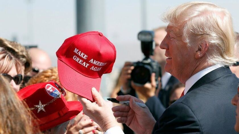 "Donald Trump stands among supporters holding a red ball cap with the words ""Make America Great Again"" on it."