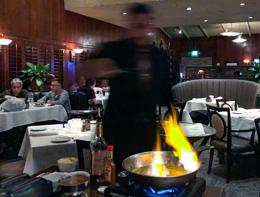 A server prepares steak Diane tableside at Dal Rae