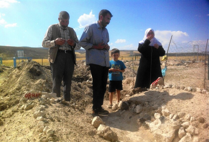 Relatives visit the graves of two Kurdish boys slain in August by Turkish security forces. Authorities accuse Muhammet Aydemir, 15, and Orhan Arslan, 17, of being Kurdish guerrillas. Their families say the pair were innocents slain in cold blood.
