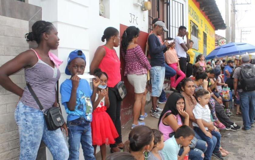 Migrantes aguardan mientras habitantes participan este miércoles en una protesta para exigir la reubicación de un edificio de la Comisión Mexicana de Ayuda a Refugiados (Comar), una dependencia que brinda refugio a miles de migrantes en el sur de México, en Tapachula, Chiapas. Los manifestantes extendieron una lona de seis metros a la salida de este organismo solicitando que no se instale ninguna oficina con fines migratorios dentro de la zona. EFE/Juan Manuel Blanco