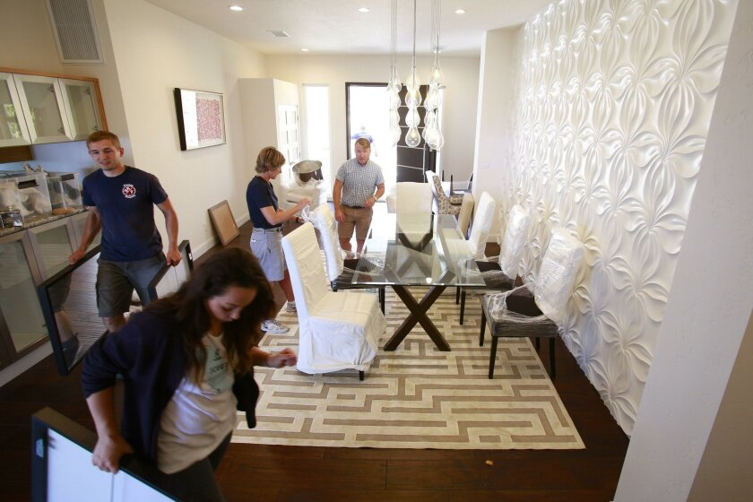Chairs and wall art are installed in a room of a staged home in La Jolla, under the direction of Scott Silvera (center).