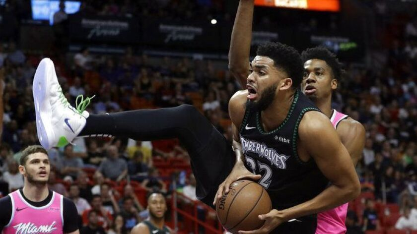 Minnesota Timberwolves center Karl-Anthony Towns (32) goes to the basket as Miami Heat center Hassan Whiteside, right, defends during the first half.
