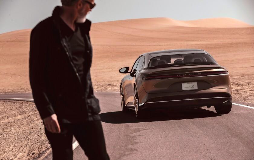 A man in the desert looks at a Lucid Air electric car in a 2020 promotional photograph.