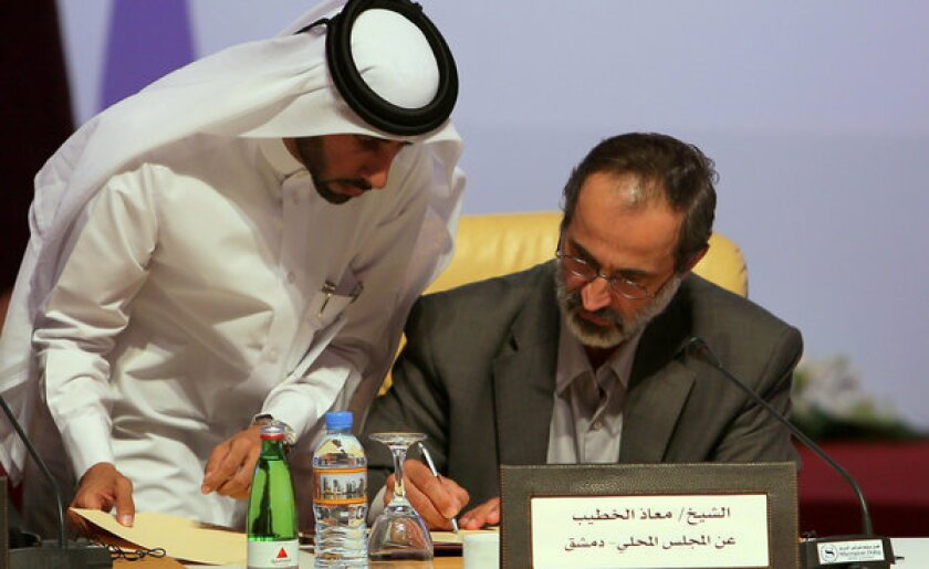 Moaz Khatib signs an agreement during a meeting to form a new Syrian opposition group in Doha, the capital of Qatar, late Sunday.