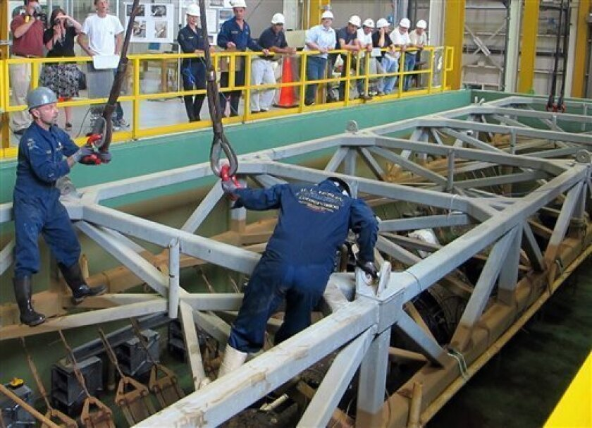 In this June 15, 2011 photo, Paul Mardikian, left, and Chris Watters, who work conserving the Confederate submarine H.L. Hunley, attach cables to the truss holding the sub before it was raised at a conservation lab in North Charleston, S.C. Raising the Hunley is the first step before the sub, which is tilted on its side and is the first in history to sink an enemy warship, can be turned upright for the first time since it went down with its crew of eight in 1864. (AP Photo/Bruce Smith)