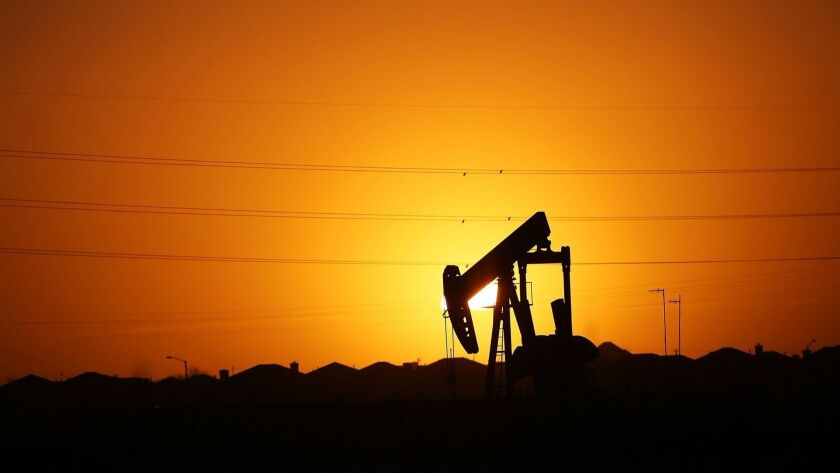 A pumpjack sits on the outskirts of town at dawn in January 2016 in the Permian Basin oil field near Midland, Texas.