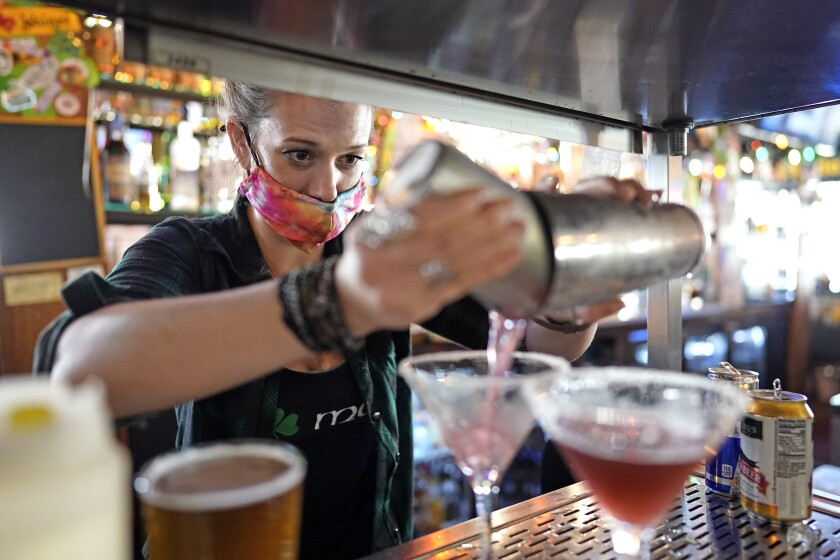 Bartender Alyssa Dooley makes a cocktail at Mo's Irish Pub, Tuesday, March 2, 2021, in Houston. Texas Gov. Greg Abbott announced Tuesday that he is lifting business capacity limits and the state's mask mandate starting next week. (AP Photo/David J. Phillip)