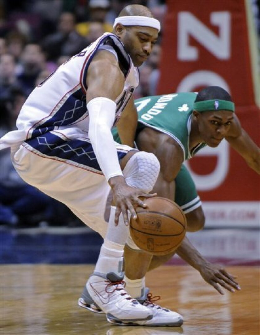 New Jersey Nets' Vince Carter, left, grabs the ball as he is pressured by Boston Celtics' Rajon Rondo during the second quarter of an NBA basketball game Saturday, Jan. 17, 2009 in East Rutherford, N.J. (AP Photo/Bill Kostroun)