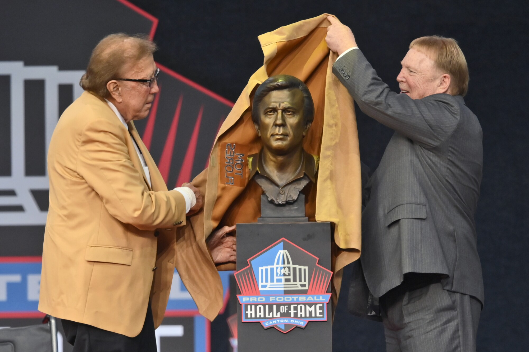 Tom Flores and Raiders owner Mark Davis unveil the bust of Flores at the induction ceremony at the Pro Football Hall of Fame.