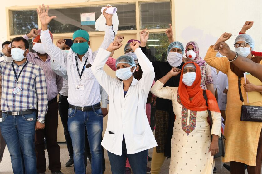 Medical staff at a hospital in Amritsar, India, protest a lack of protective gear and coronavirus testing kits Friday.