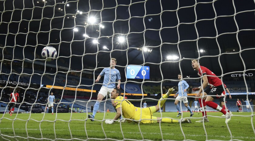Manchester City's Kevin De Bruyne, left, scores his side's opening goal during the English Premier League soccer match between Manchester City and Southampton at the Etihad Stadium in Manchester, England, Wednesday, March 10, 2021. (Clive Brunskill/Pool via AP)
